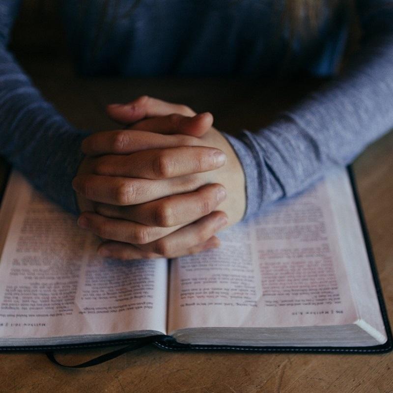 Zum Gebet gefaltete Hände auf einer aufgeschlagenen Bibel