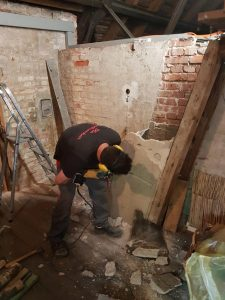 Einsatz des Schlagbohrers beim Entfernen des alten Kamins der Umluftheizung auf dem Dachboden der Stephanuskirche Nürnberg Gebersdorf