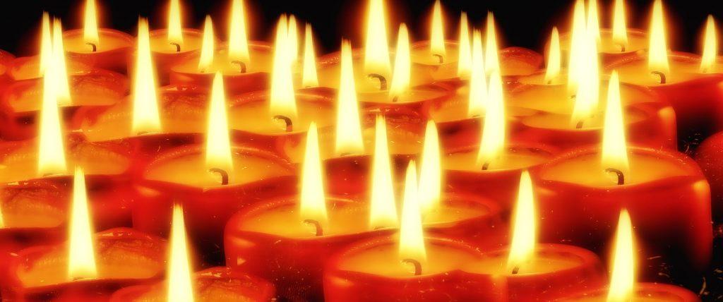 Eine vielzahl von brennenden Kerzen die ganz nahe zusammenstehen (Symbolfoto)