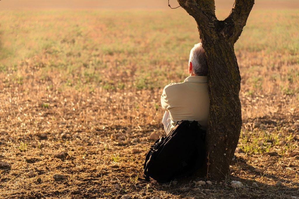Mann lehnt mit dem Rücken an einem Baum und schaut einsam in die Ferne - Symbolfoto