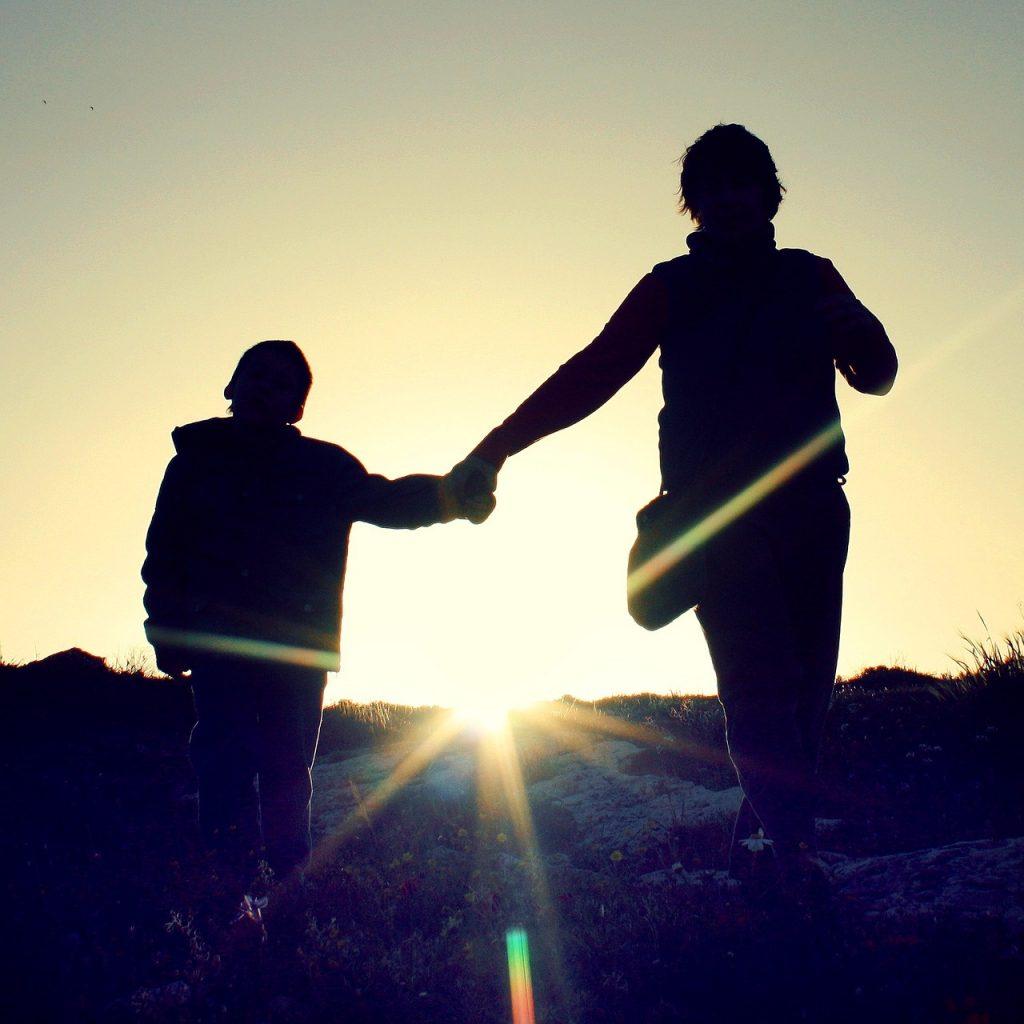 Symbolbild: Silhouette von einem Elternteil mit Kind, die sich an den Händen halten und dem Sonnenaufgang entgegenlaufen