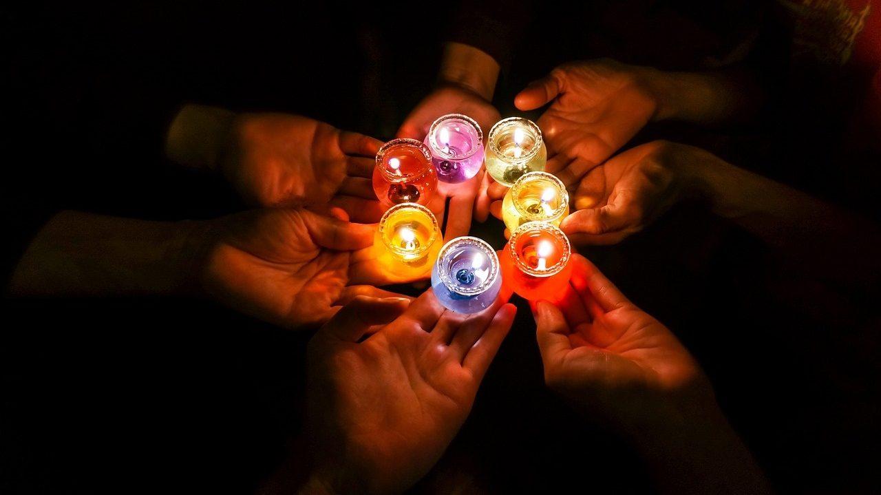 Symbolbild: Mehrere Hände halten bunte Kerzen in der Dunkelheit
