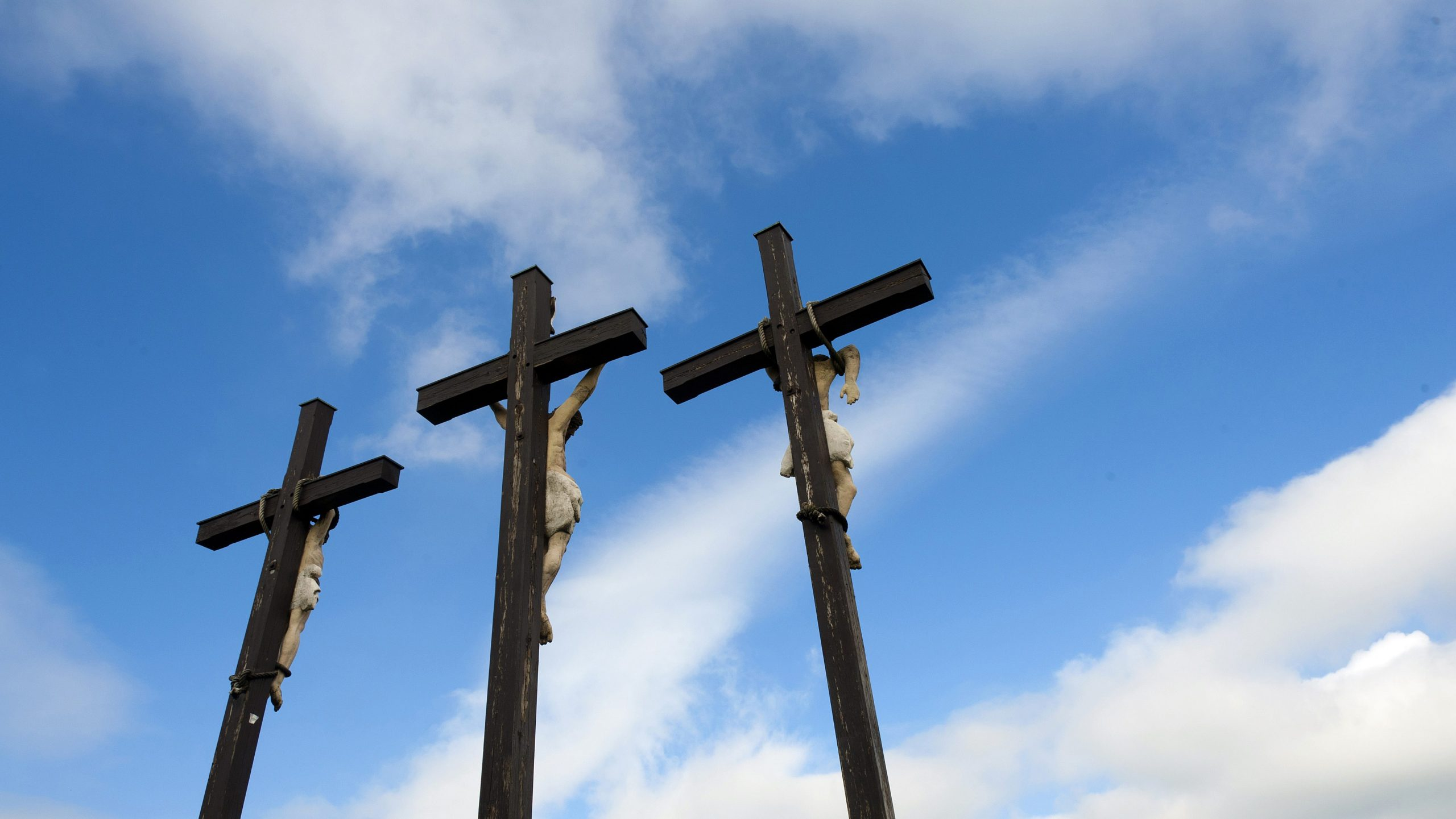Drei Kreuze an denen drei Statuen symbolisch gekreuzigt wurden. Der Blick des Betrachters geht in Richtung Himmel, die Kreuze sind von der Rückseite aus zu sehen.