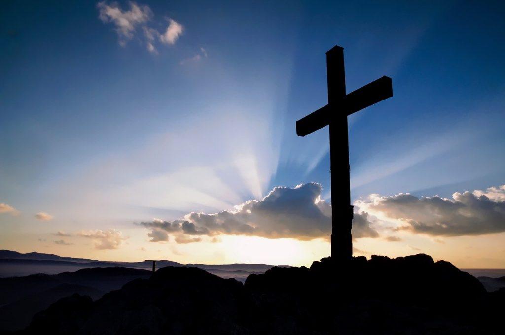 Leeres Kreuz auf einem Berg bei Sonnenaufgang - Symbolbild