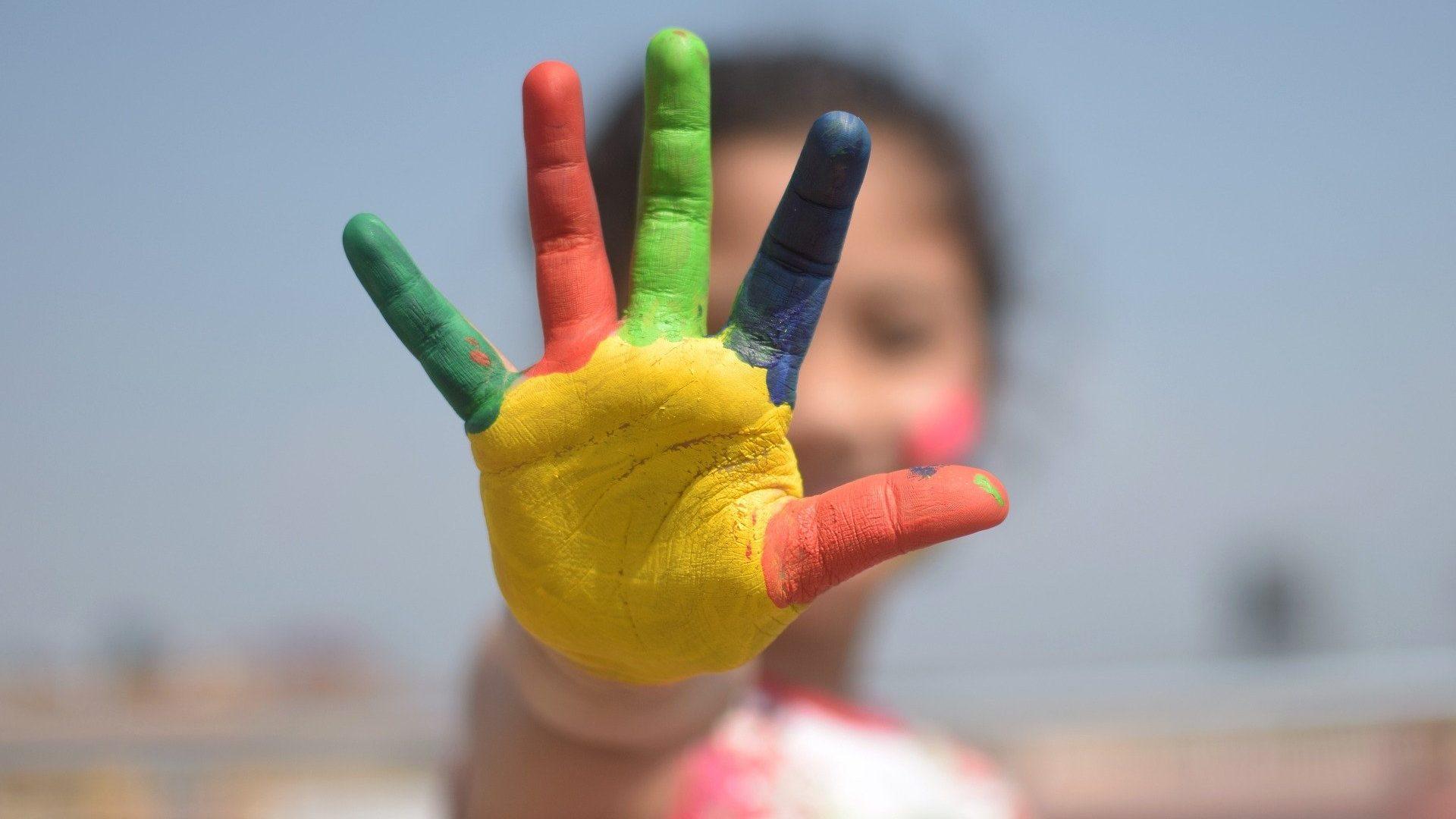 Symbolbild Kind hält eine bunt bemalte Hand in die Kamera