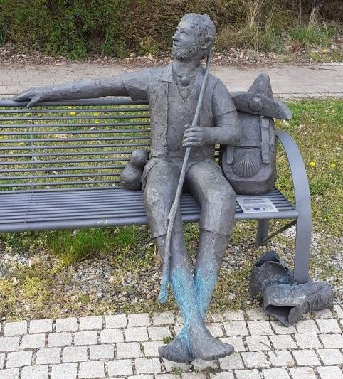 Skulptur, welche einen Wanderer darstellt, sitzt auf einer Bank und ruht sich aus.