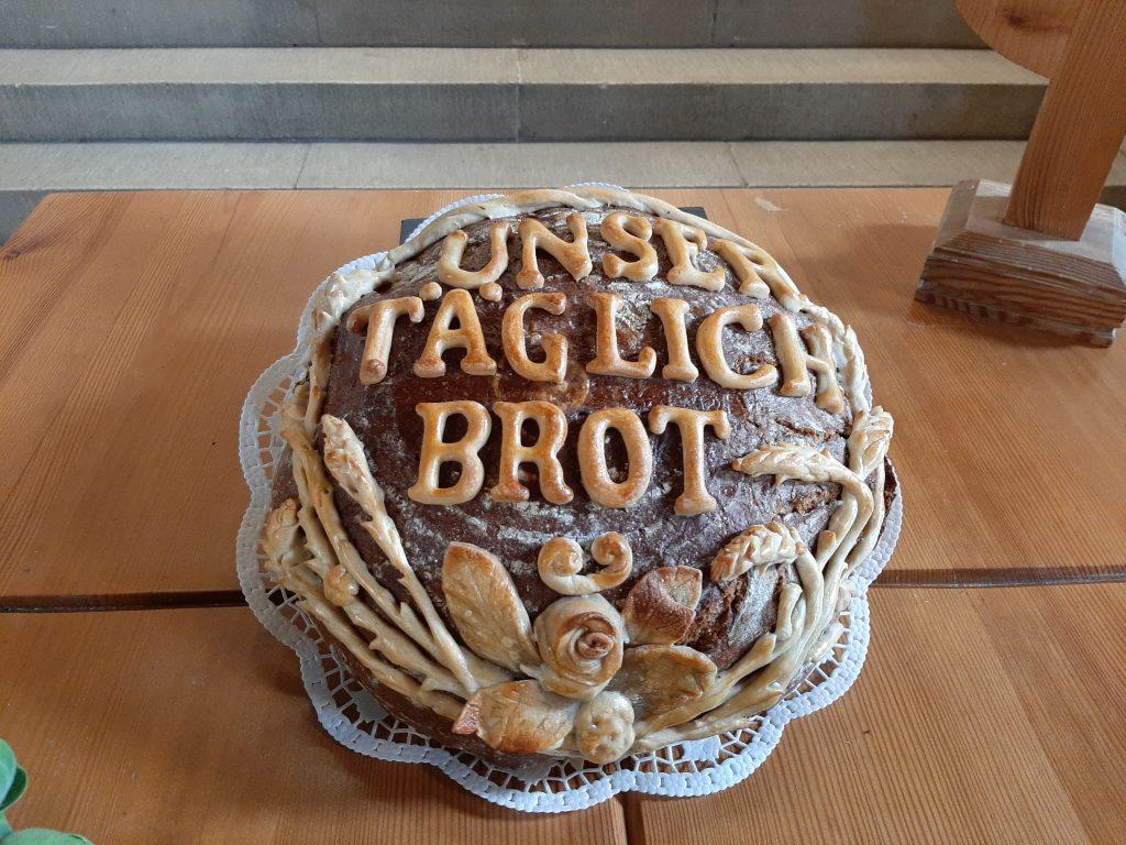 """Brot auf dem Altar der Stephanuskirche mit der Aufschrift """"UNSER TÄGLICH BROT"""""""