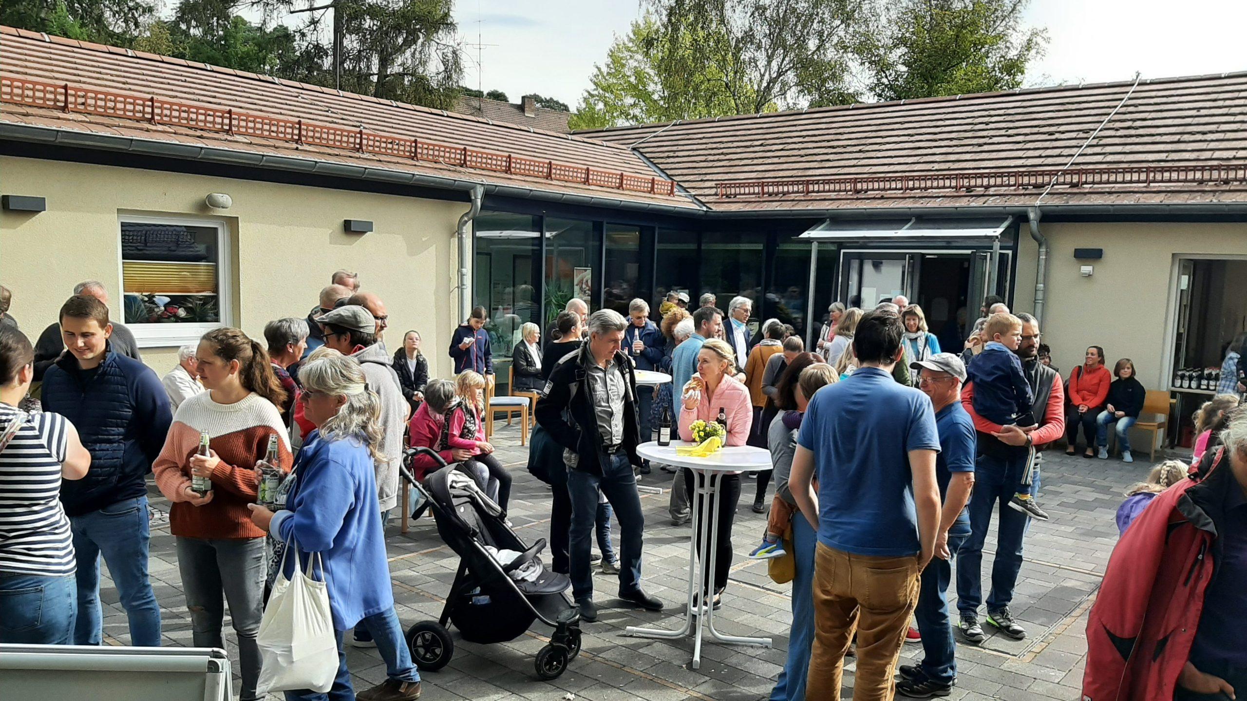 Menschen versammeln sich vor dem Gemeindehaus der Stephanuskirche Nürnberg Gebersdorf nach dem Erntedankgottesdienst um das Gemeindefest zu feiern.