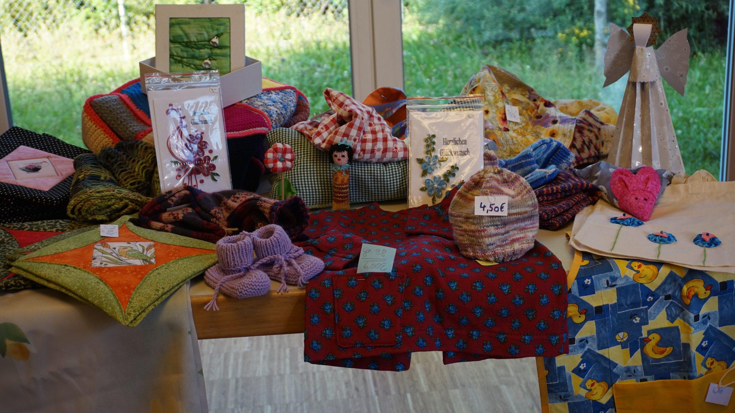 Verschiedene Produkte die durch den Bastelkreis der Stephanuskirche in Handarbeit erzeugt wurden. Unter anderem Grußkarten, Socken, Taschen, Papierengel, Decken und Tücher.