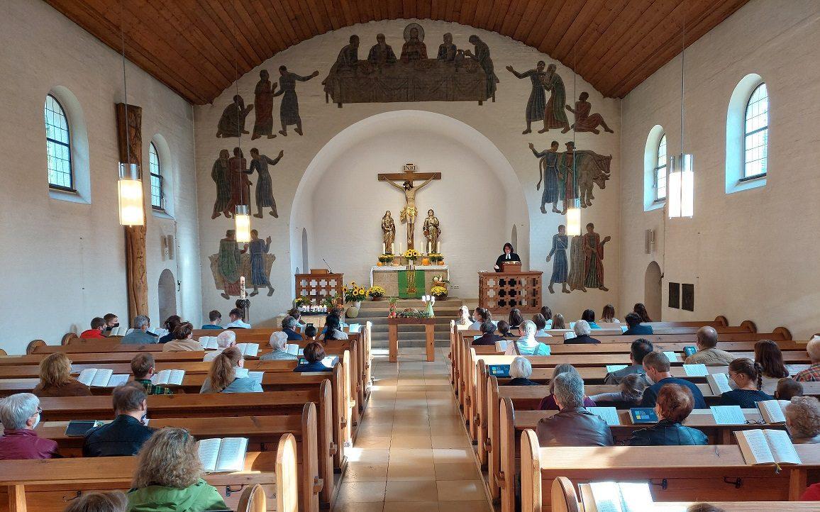 Innenansicht der Stephanuskirche Nürnberg Gebersdorf während eines Gottesdienstes. Der Blick geht vom Eingangsbereich Richtung Altarraum.