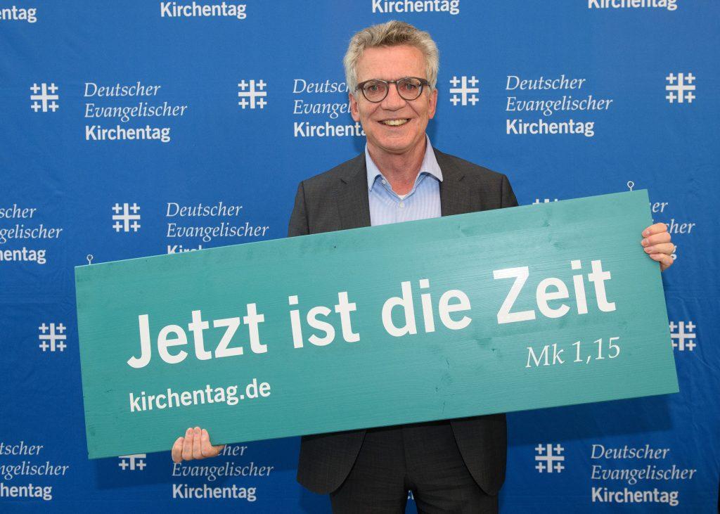 """Thomas de Maiziere hält ein Schild mit der Losung """"Jetzt ist die Zeit"""" (Mk 1,15) für den 38. Deutschen Evangelischen Kirchentag 2023 in Nürnberg in den Händen"""